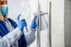 Woman Houseworker portrait in rubber blue gloves clean Door knob by cloth rag. Cleaning front door handle by antibacterial alcohol spray. New normal Covid 19 coronavirus in Surfaces disinfection.