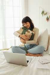 Woman hugging her christmas present sitting on bed at home. Happy woman sitting on bed doing a video call talking to family and friends for christmas.
