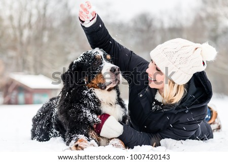 Woman hugging her dog in the snow on winter day