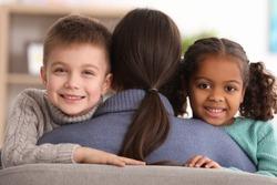 Woman hugging little kids indoors. Child adoption
