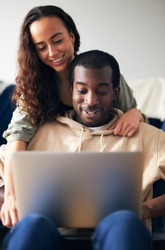 Woman hugging man from behind as young mixed ethnicity couple relax on sofa at home browsing internet on laptop
