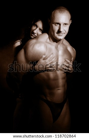 Woman hugging muscular man on a dark background