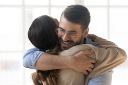 Woman hugs man close up view, smiling millennial couple embracing glad to see each other after long separation, greet at meeting expressing care and bonding, friendship and good warm relations concept
