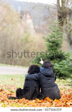 Woman hugs the beautiful Newfoundland in the park. Rear view. #507506359