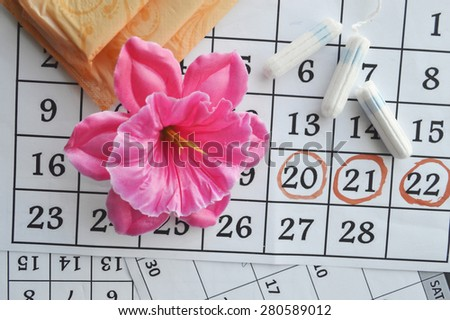Woman hygiene protection, close-up.menstruation calendar with cotton tampons,orange Gerber,Sanitary pads on a red background