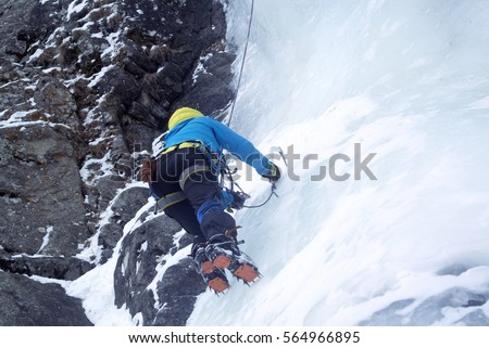 Woman ice climbers climb a frozen waterfall in a blue jacket with ice tools #564966895