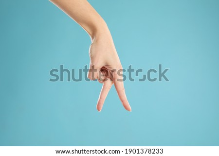 Woman imitating walk with hand on light blue background, closeup. Finger gesture Stockfoto ©
