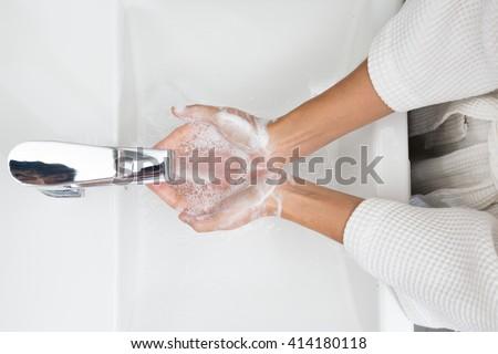 Woman in a bathrobe is washing hands,Hygiene. Cleaning Hands. Washing hands.