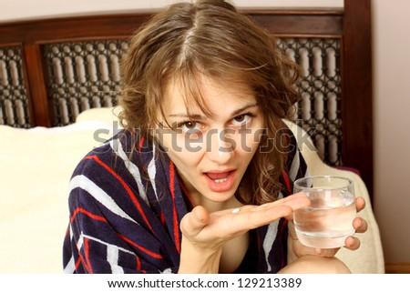 woman in a bathrobe suffering from a headache #129213389
