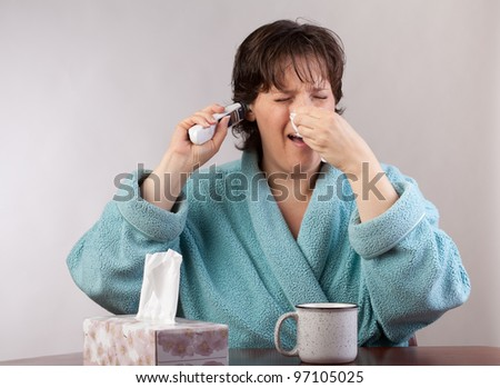 Woman in a bathroom with a bad cold taking her temperature - stock photo