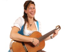 Woman in a Bavarian Dirndl and with a guitar