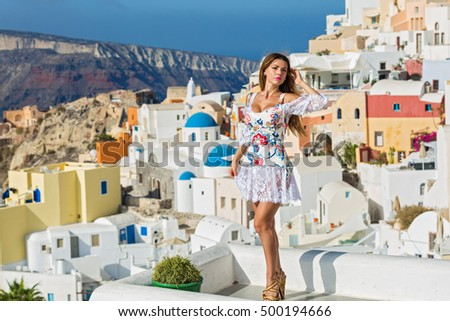 Woman in a beautiful dress on a background architecture of Santorini #500194666