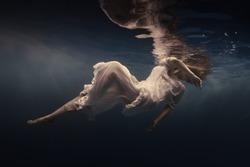 Woman in a beautiful dress swims underwater