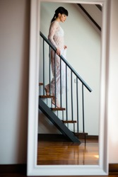 Woman in a beautiful lace nightgown walking downstairs in the morning at home. Close up woman feet on stairs.