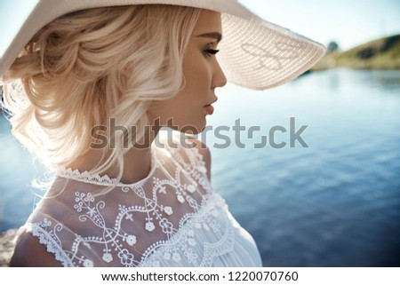 Woman in a big white hat stands near the sea, a blonde in a hat looking at the lake, summer vacation travel and vacation. Sun rays at sunset #1220070760