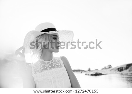 Woman in a big white hat stands near the sea, a blonde in a hat looking at the lake, summer vacation travel and vacation. Sun rays at sunset #1272470155