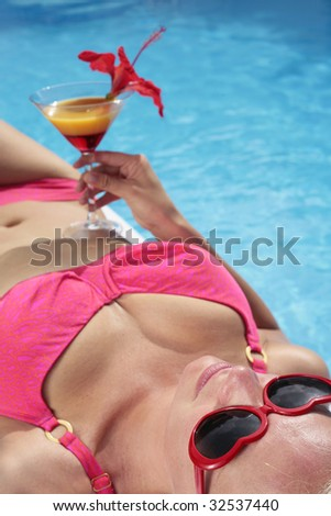 Woman in a bikini with a cocktail by a blue swimming pool