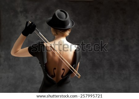 Stock Photo Woman in a black dress and black hat plays the violin. Photo compilation, photo and hand-drawing elements combined