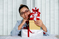 Woman in a blue shirt holding gift boxes tied with a red ribbon present for the festival of giving special holidays like Christmas, Valentine's Day.