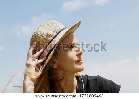 woman in a borsalino hat enjoying the summer sun on the coast Stock photo ©