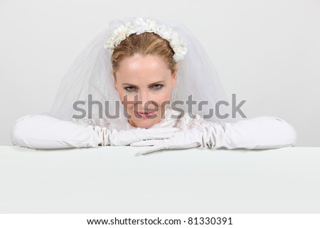 Woman in a bridal gown leaning on a white board