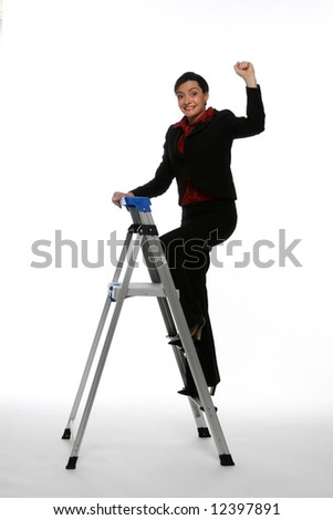 Woman in a business suit climbing up a step ladder with her fist in the air while smiling at the camera. Isolated against a white background