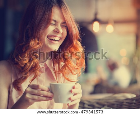 Woman in a cafe. Young redheaded woman with a mug of tea in his hands and laughs. Laugher #479341573