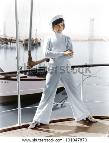 Woman in a captains hat standing on top of a sailboat