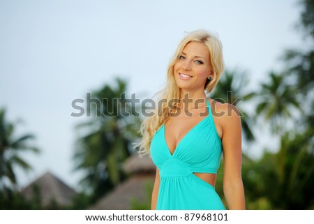 woman in a dress on a background of palm trees