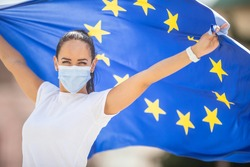 Woman in a face mask holding an European union flag behind her back with arms up.