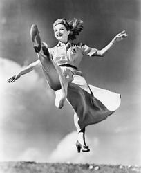 Woman in a flowing dress leaping through the air