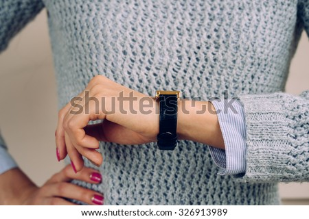 Woman in a gray sweater checks the time on a wrist watch close-up.