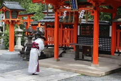 Woman in a kimono bowing in prayer in a Japanese shinto shrine (Fushimi inari shrine)