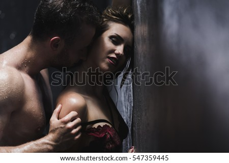 Woman in a lace bra is standing back to man during shower