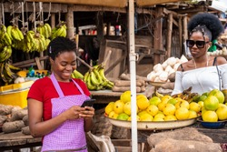 woman in a market smiling while using her phone