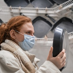 Woman in a medical face mask chooses a frying pan in the store