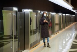 Woman in a medical face mask to avoid the spread of coronavirus is waiting for a train and holding a phone at the subway station. A girl in a surgical mask against COVID-19 is keeping social distance.