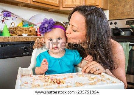 Woman in a messy kitchen kisses her baby
