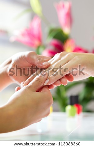 Woman in a nail salon receiving a manicure by a beautician, she is getting a hand massage - stock photo