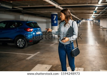 Woman in a parking garage, unlocking in her car. Woman activating her car alarm in an underground parking garage as she walks away. Business woman walking with car keys in the underground parking