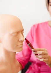 Woman in a pink medical uniform shows with marker on a human head anatomy model. Education, anthropology,science, anatomy concept.