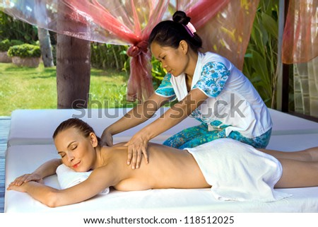 Woman in a prone position, getting a back massage from a thai masseuse inside a spa hut, grass and trees visible in the background.