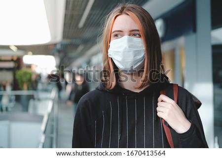 Woman in a protective face mask at public place. Coronavirus, COVID-19 spread prevention concept, responsible social behaviour of a citizen