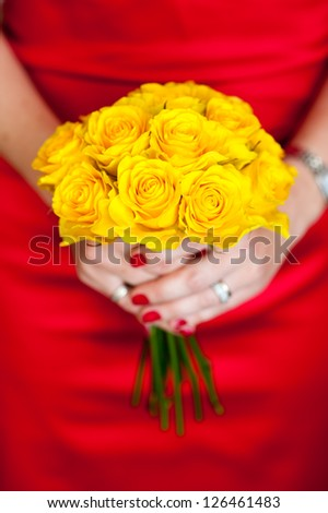 woman in a red dress holding a yellow bouquet of roses