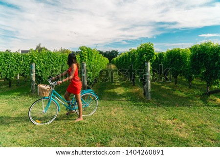 Woman in a red dress riding a bicycle in vineyards. View of grapevines Shot in Blenheim, South Island, New Zealand. #1404260891