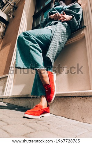 Woman in a red stylish suede loafer shoes, blue jeanse, white shirt and trendy checkered coat posing on the street. Pair of trendy female loafers shoes. Stock fotó ©