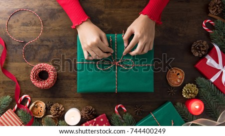 Woman in a red sweater wrapping gift box with equipment and decorating items on wood table, preparing for celebrating Christmas holidays - top view.