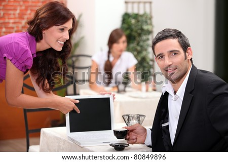 Woman in a restaurant pointing to a computer screen left blank for your image