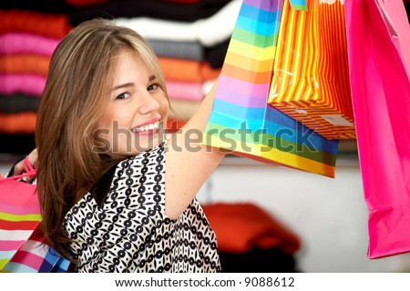 woman in a retail store smiling and carrying shopping bags