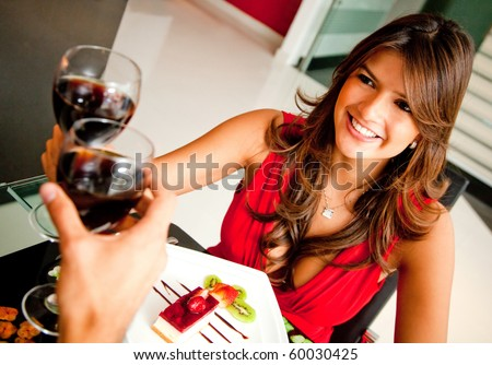 Woman in a romantic dinner toasting with wine
